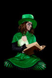 Green goblin is reading from a book, black background, concept f stock photo