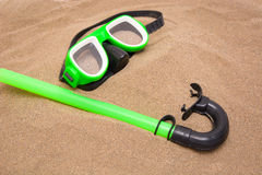 Green goggles and snorkel tube on sand Stock Photo