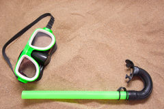Green goggles and snorkel tube on sand Royalty Free Stock Photography