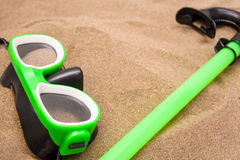 Green goggles and snorkel tube on sand Royalty Free Stock Photo