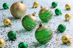 Green and gold christmas balls. On blue background with colorful shiny decor stars. Christmas and New Year concept. Selective focus Royalty Free Stock Photos