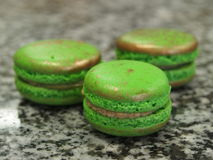 Three macaron cookies, green gold Stock Images