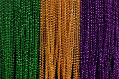 Green, gold, and purple Mardi Gras beads. Background
