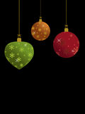 Green gold and red christmas baubles on black Royalty Free Stock Photos