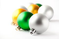 Green, gold and silver Christmas baubles on white Royalty Free Stock Photography