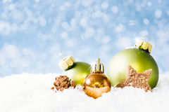 Green and Golden Christmas Balls on Snow Royalty Free Stock Image