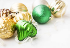Green and golden Christmas ornaments with pearly globes and ribb Stock Photos