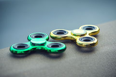 Green and golden fidget spinner relieving toy Royalty Free Stock Photos