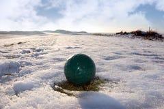 Green golf ball on cloudy snow covered golf course Stock Photos