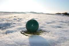 Green golf ball on snow covered golf course royalty free stock photo