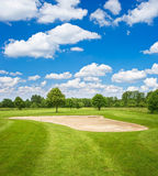 Green golf course and blue cloudy sky Stock Photography