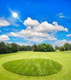 Green golf course and blue sunny sky Stock Photos