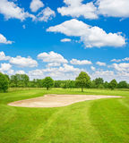 Green golf course field and blue cloudy sky Royalty Free Stock Photos
