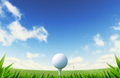 Green Golf court with close up on grass and ball on tee. Background out of focus, with red flag on a distance and blue sky with fluffy clouds Stock Image