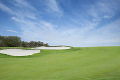 Green golf fairway with sand traps below blue sky with clouds Stock Photos
