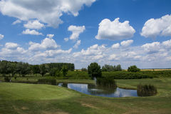 Green golf field and blue cloudy sky. Green golf field and blue  sky Stock Photos