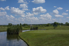 Green golf field and blue cloudy sky Stock Photos