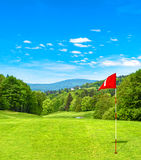 Green golf field and blue sky. Golf course red flag Stock Photo
