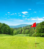 Green golf field and cloudy blue sky Stock Image
