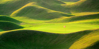 Green golf field with lights and shadows. A red flag is flying with a focus Stock Photos