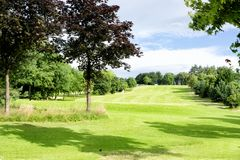Green golf field with green trees. Green golf field in Alexandra park in Glasgow, Scotland, UK Stock Image