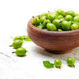 Green gooseberries in a ceramic bowl on an old wooden table Royalty Free Stock Images