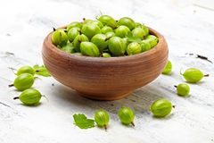 Green gooseberries in a ceramic bowl on an old wooden table Stock Image