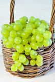 Green grape in basket on wooden table Royalty Free Stock Photos