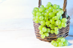 Green grape in basket on wooden table Royalty Free Stock Image