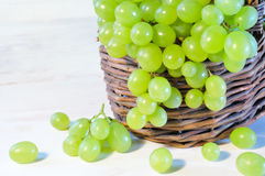 Green grape in basket on wooden table Stock Photos
