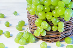 Green grape in basket on wooden table Royalty Free Stock Images