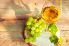 Green grape and one glass of white wine in the vineyard Royalty Free Stock Photo