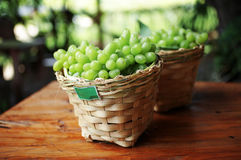 Green grape in wooden basket Stock Photos
