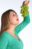 Green grapes. Young woman cannot wait to eat some green grapes Stock Image