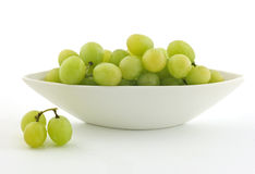 Green grapes. In boat shaped white dish on white background Royalty Free Stock Photography