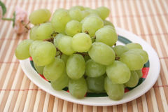 Green grapes. Some fresh green grapes on a plate stock photos