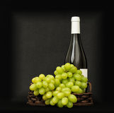 Green grapes in a basket and bottle Stock Photography
