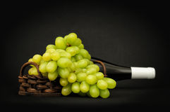 Green grapes in a basket and bottle Stock Images