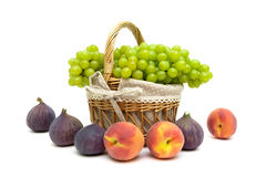 Green grapes in a basket, peaches and figs on a white background Stock Image