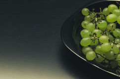 Green grapes in a black plate Royalty Free Stock Photos