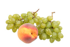 Green grapes bunch and one orange peach. Royalty Free Stock Photography