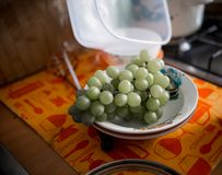 Green grapes are in a dish that stands in the kitchen royalty free stock image