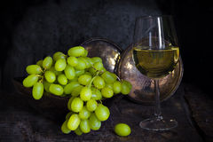 Green grapes and a glass of white wine Stock Photos