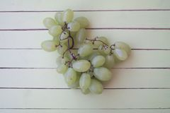 Green grapes on green wood from above stock photo
