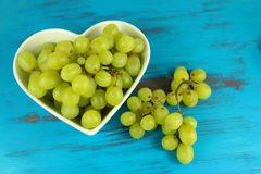 Green grapes in heart shaped bowl on a turquoise wood background Stock Image