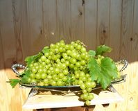 Green grapes with leaves on a beautiful dish Stock Photo