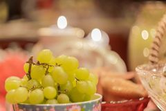 Green grapes on a table amidst smoldering candles.  Stock Image