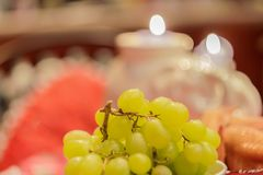 Green grapes on a table amidst smoldering candles.  Royalty Free Stock Photo
