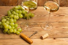 Green grapes and white wine glasses. Bunch of green grapes and white wine glasses royalty free stock photo