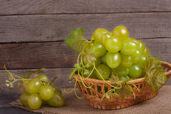 Green grapes in a wicker basket on wooden table. Green grapes in a wicker basket on a wooden table stock image